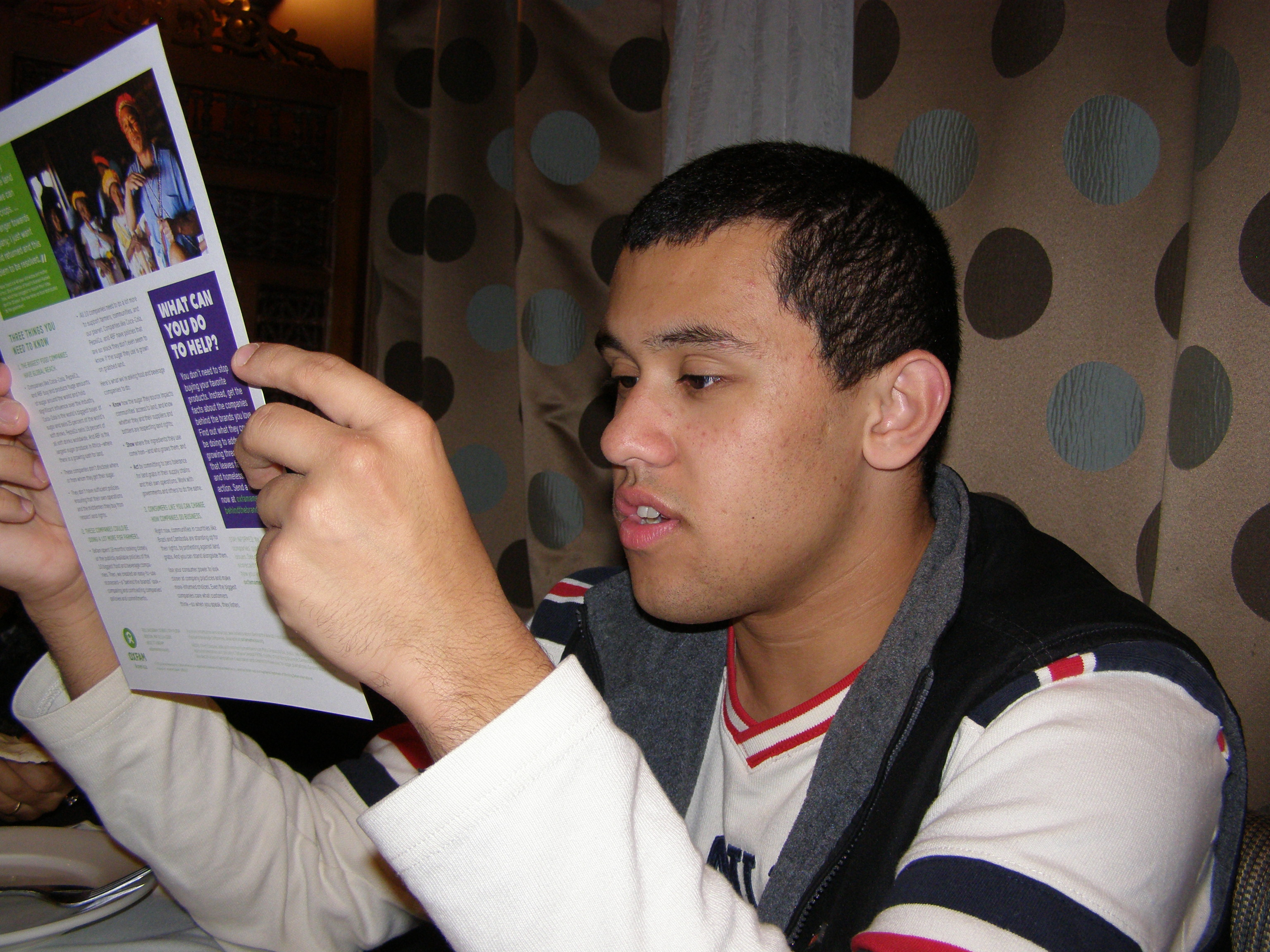 Ari reading World Food Day brochure